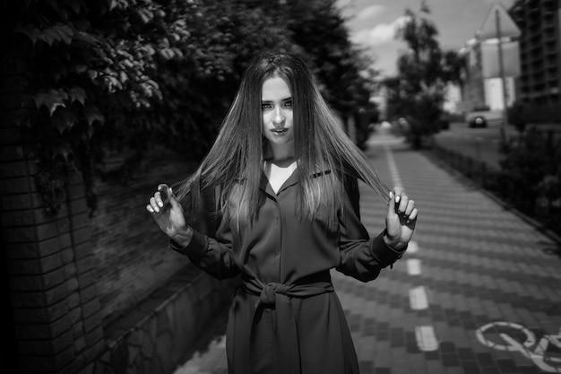 Foto preto e branco do vestido vestindo da mulher atrativa em um fundo da estrada. cabelo longo. retrato de uma menina bonita. jovem sessão fotográfica feminina.