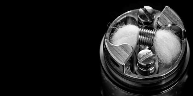Foto preto e branco e monocromática de uma única micro bobina com mecha de algodão orgânico japonês no atomizador de tanque de gotejamento rebuildable de ponta para caçador de sabores, dispositivo vaping, dispositivo vap, equipamento vape, equipamento de vaporizador