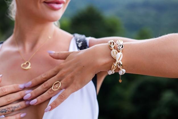 Foto próxima das mãos da mulher com um anel e uma pulseira com joias