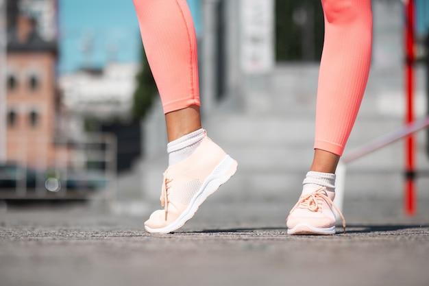 Foto próxima das pernas da mulher usando tênis esportivos cor de rosa e leggings