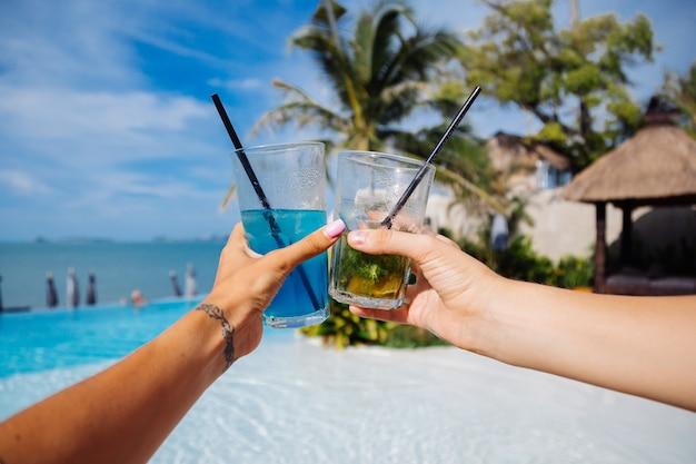 Foto próxima de mãos segurando coquetéis de álcool