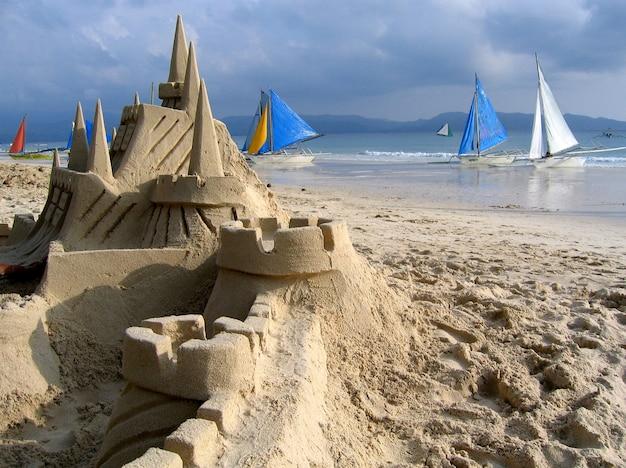 Foto próxima de um castelo de areia em uma praia com barcos ao fundo