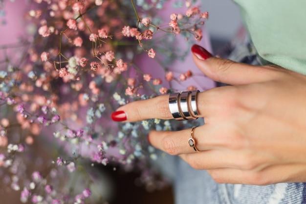 Foto próxima dos dedos da mão de uma mulher usando dois anéis, buquê de flores coloridas