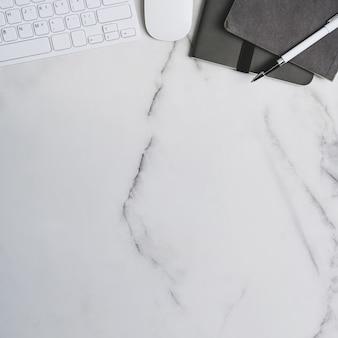 Foto quadrada do espaço de trabalho com teclado, caderno, mouse e espaço de cópia na mesa de mármore.