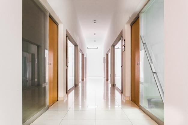 Foto quadrada do longo corredor em casa com portas