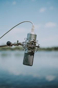 Foto rasa vertical de microfone de gravação cinza com um fio