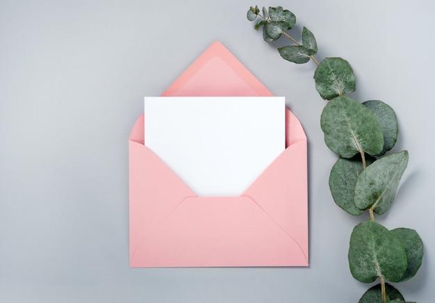 Foto real. maquete de cartão de convite quadrado envelope rosa com um galho de eucalipto. vista superior com espaço de cópia, plano de fundo cinza claro. modelo para branding e publicidade