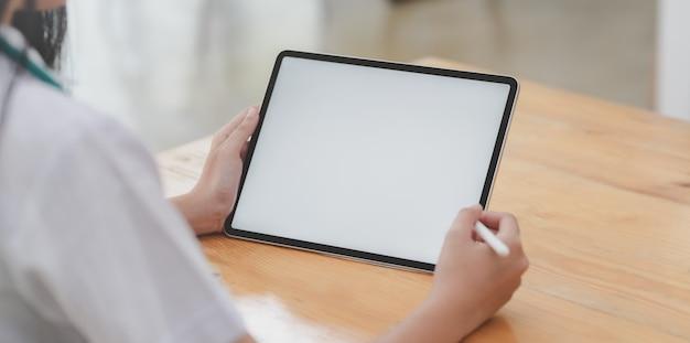 Foto recortada da jovem médica examinando o prontuário do paciente enquanto estiver usando o tablet