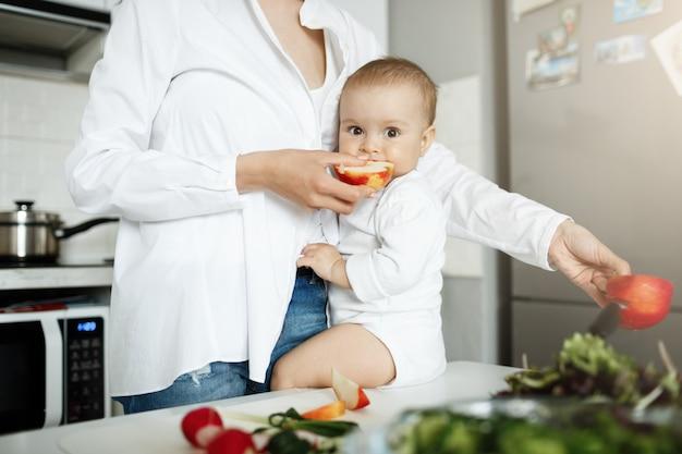 Foto recortada da mãe dando uma fatia de maçã ao bebê