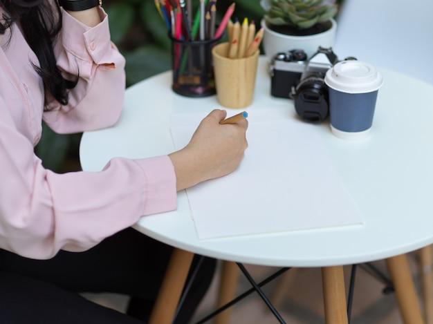 Foto recortada da mão de uma aluna desenhando em um papel simulado na mesa de centro de um café