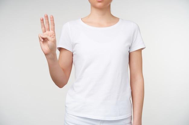 Foto recortada da mão de uma jovem mulher com manicure nua mostrando três dedos enquanto significa a letra w, em pé sobre um fundo branco em roupas casuais