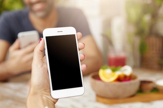 Foto recortada da mão de uma mulher caucasiana, segurando o telefone móvel genérico