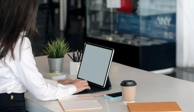 Foto recortada da mão de uma mulher digitando no teclado do tablet enquanto está sentado na mesa do escritório, tela em branco para design gráfico.