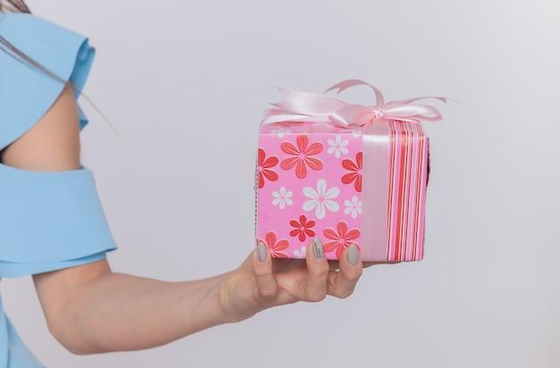 Foto recortada da mão de uma mulher segurando um presente e comemorando o dia internacional da mulher em pé sobre uma parede branca