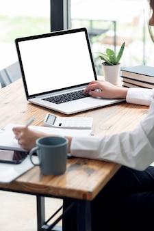 Foto recortada da mão de uma mulher trabalhando no computador laptop no escritório, laptop de tela em branco de maquete para exibição de produto, vista vertical,