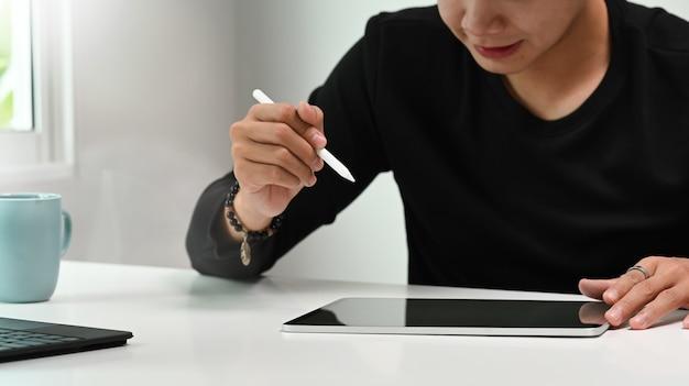Foto recortada da mão do designer gráfico ou fotógrafo segurando a caneta stylus de desenho na mesa digitalizadora.