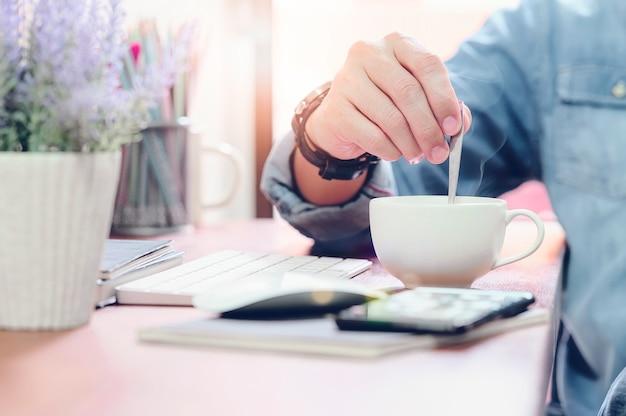 Foto recortada da mão do homem segurando a colher enquanto bebe café quente no café.