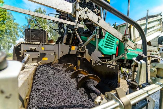 Foto recortada da máquina com asfalto fresco. asfalto lisonjeiro. foco seletivo na técnica pesada.