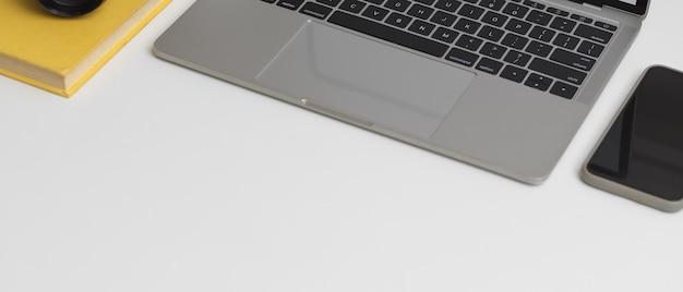 Foto recortada da mesa de trabalho com laptop, smartphone, livro de programação e espaço de cópia