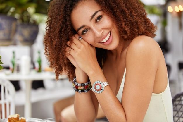 Foto recortada da modelo feminina de pele escura com sorriso largo e penteado afro, em alto astral, recria na cafeteria