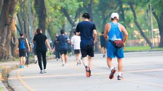 Foto recortada da vista de costas de pessoas correr e caminhar no parque do jardim pedonal.