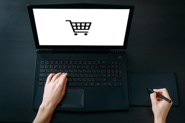 Foto recortada das mãos do designer gráfico trabalhando com tablet gráfico e laptop na mesa preta do escritório