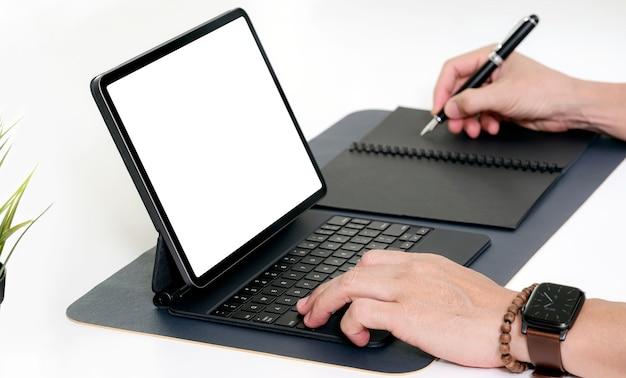 Foto recortada das mãos do homem trabalhando no teclado do tablet e escrevendo no caderno enquanto está sentado à mesa.