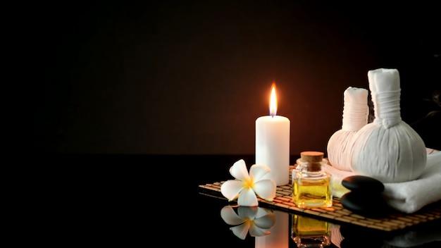 Foto recortada de acessórios de tratamento de spa com toalha branca, vela e óleo de aroma em fundo escuro