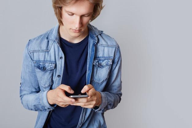 Foto recortada de adolescente do sexo masculino em camisa jeans, possui telefone inteligente moderno, joga online, navega em redes sociais e escreve posts, sendo viciada em internet. cara hipster se comunica com os amigos