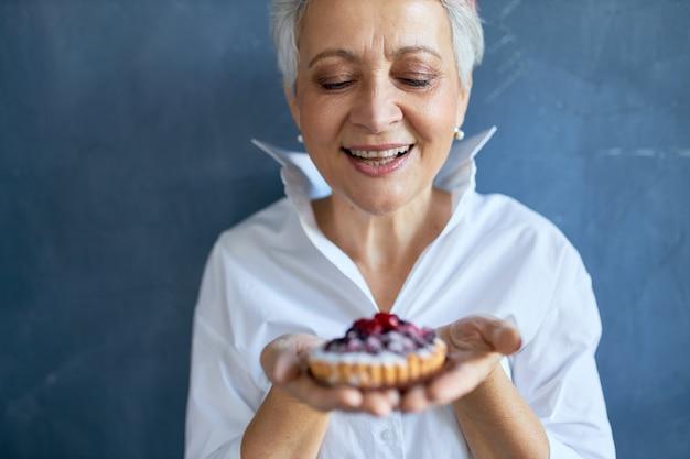 Foto recortada de alegre avó atraente em camisa branca, segurando um pedaço de torta de baga recém-assada para aniversário, com expressão facial alegre, sorrindo amplamente.