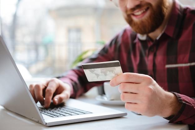 Foto recortada de alegre barbudo jovem segurando o cartão de débito.