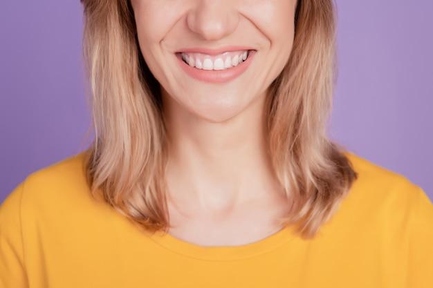 Foto recortada de alegre positiva simpática linda garota sorrindo com os dentes radiantes mostrando os dentes branqueados isolados sobre o fundo de cor violeta