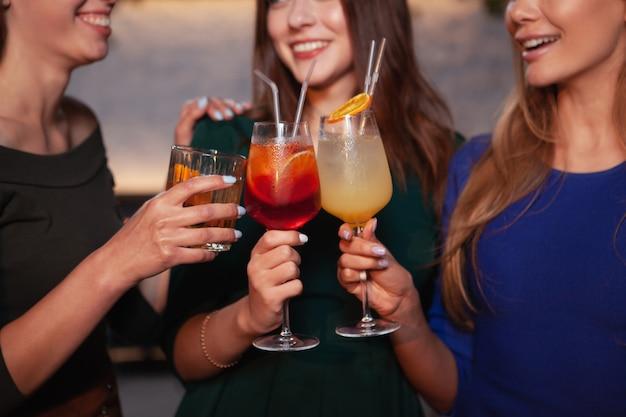Foto recortada de amigas felizes tilintar de copos de coquetel juntos, comemorando juntos