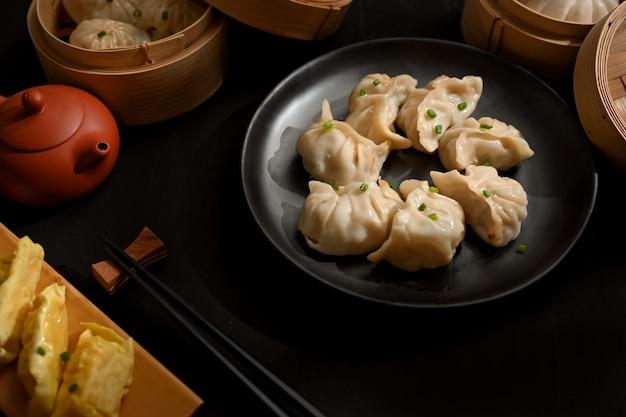 Foto recortada de bolinhos de dimsum em um prato de cerâmica preta na mesa de jantar de um restaurante chinês