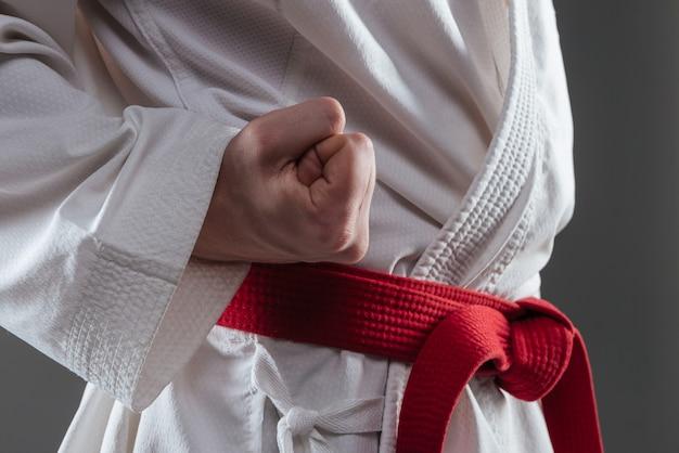 Foto recortada de bonito desportista vestido de quimono, pratica caratê e gesto com a mão isolada sobre fundo cinza.