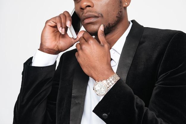 Foto recortada de bonito empresário africano falando ao lado de seu telefone. isolado sobre fundo branco.