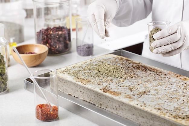 Foto recortada de cientista com luvas brancas conduzindo experimento farmacêutico