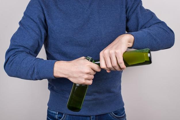 Foto recortada de close-up de um participante habilidoso mostrando seu talento ao abrir garrafas em fundo cinza isolado