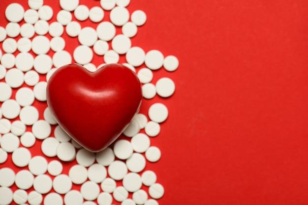 Foto recortada de close-up de um pequeno coração deitado no fundo com pequenas pílulas redondas copie o espaço em branco