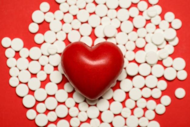 Foto recortada de close-up de um pequeno coração deitado no fundo com pequenas pílulas redondas