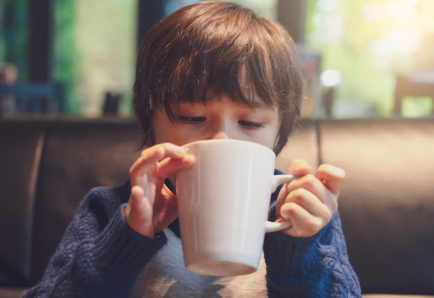 Foto recortada de criança bebendo chocolate quente no café com um tom quente, menino saudável criança soprando bebida quente na cafeteria no inverno.