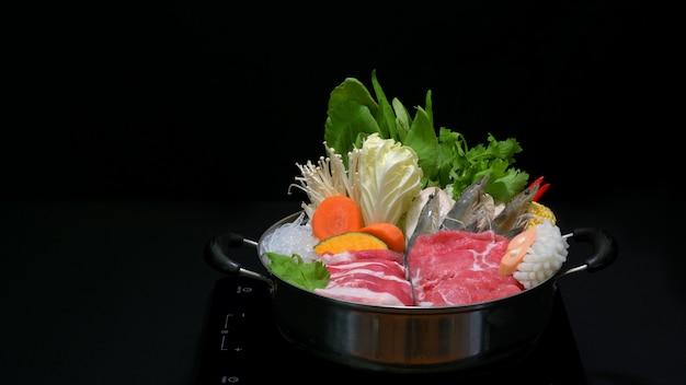 Foto recortada de delicioso shabu shabu em uma panela quente com fundo preto