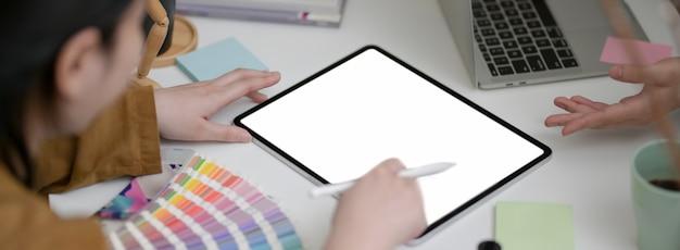 Foto recortada de designer feminina de brainstorming em seu projeto com tablet mock-up e suprimentos de designer