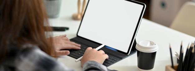 Foto recortada de designer gráfico feminino digitando no tablet de tela em branco na mesa de trabalho