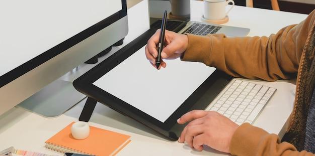 Foto recortada de designer masculino, editando seu projeto no tablet digital de tela em branco em seu escritório moderno