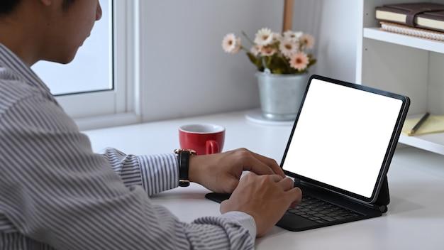 Foto recortada de designer masculino está trabalhando com tablet de computador em seu espaço de trabalho criativo.