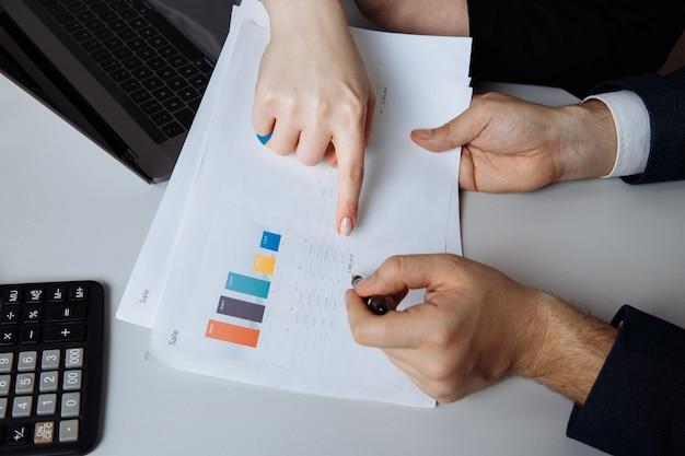 Foto recortada de dois colegas trabalhando com um laptop e documentos na mesa branca na sala do escritório