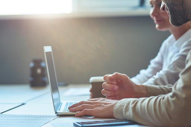 Foto recortada de dois colegas usando um laptop enquanto estão sentados à mesa em um escritório moderno, trabalhando