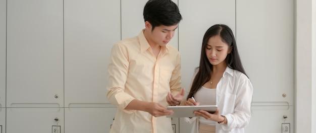 Foto recortada de dois estudantes universitários consultando suas tarefas