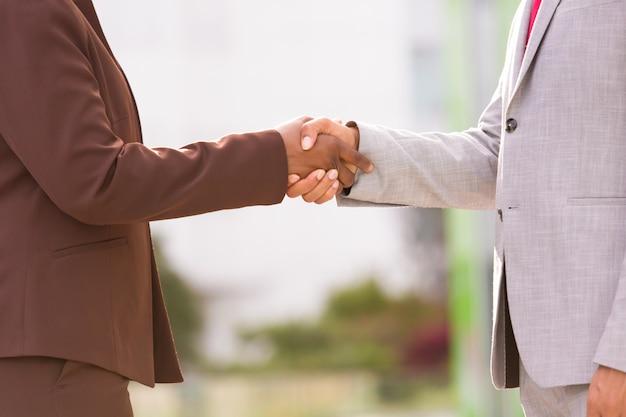 Foto recortada de duas pessoas, apertando as mãos